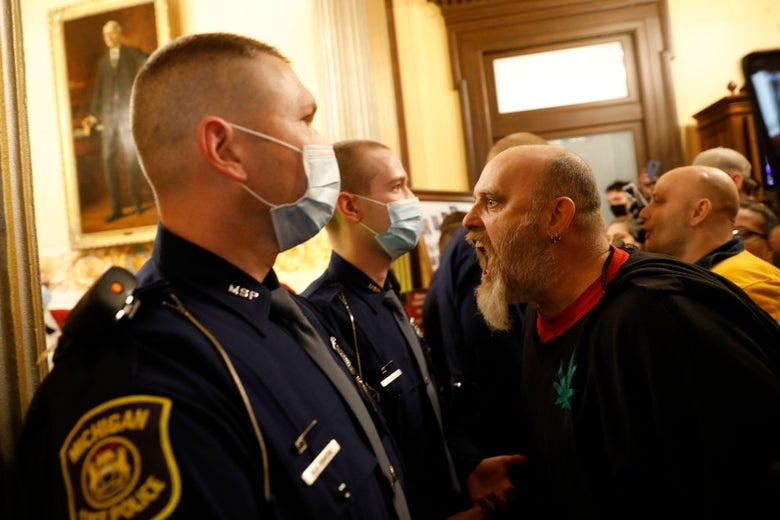White man screaming at a police officer wearing a mask