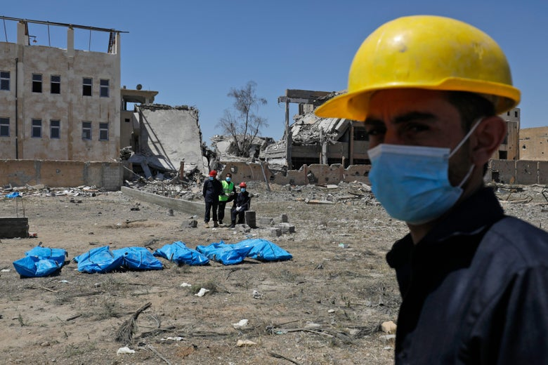 Syrians wearing hard hats and surgical masks retrieve bodies from a mass grave next to a ruined building.