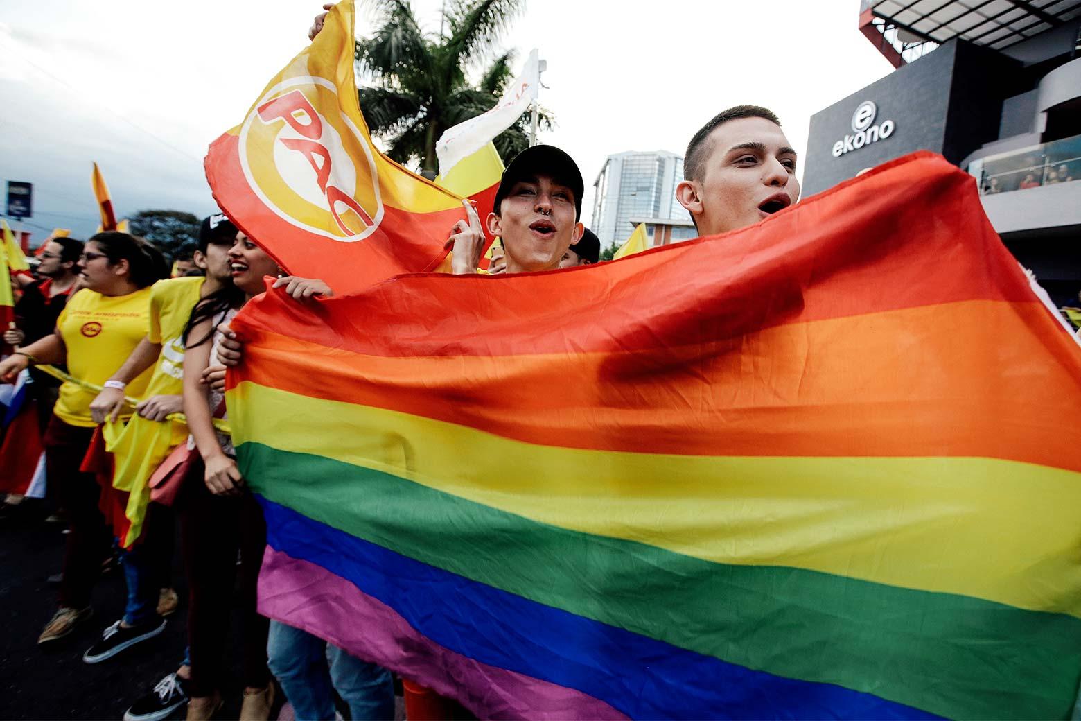 Supporters of Carlos Alvarado Quesada hold up a rainbow LGBTQ pride flag.