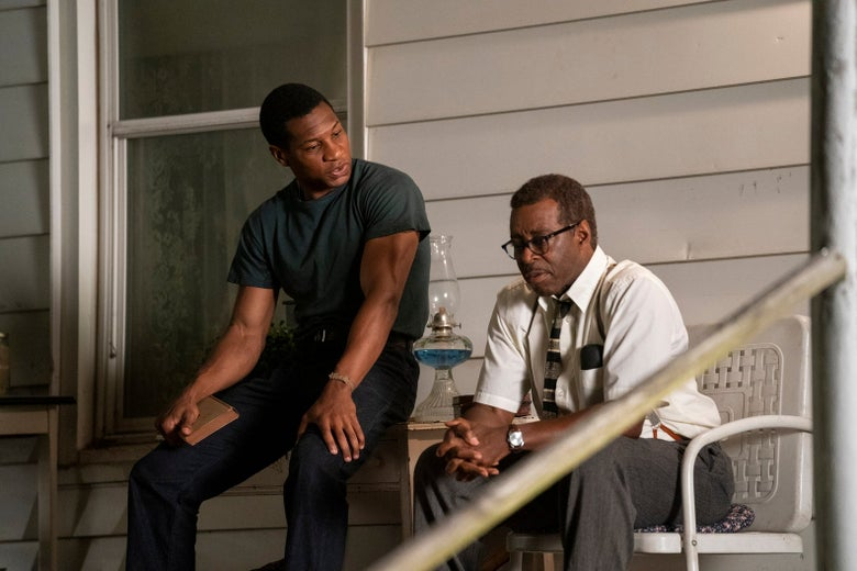 Jonathan Majors and Courtney B. Vance sit on a porch in HBO's Lovecraft Country.