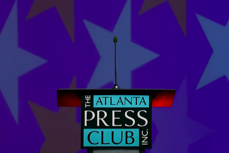 A microphone emerges atop on a podium that says the Atlanta Press Club Inc. It is in front of a blue background with large red and white stars.