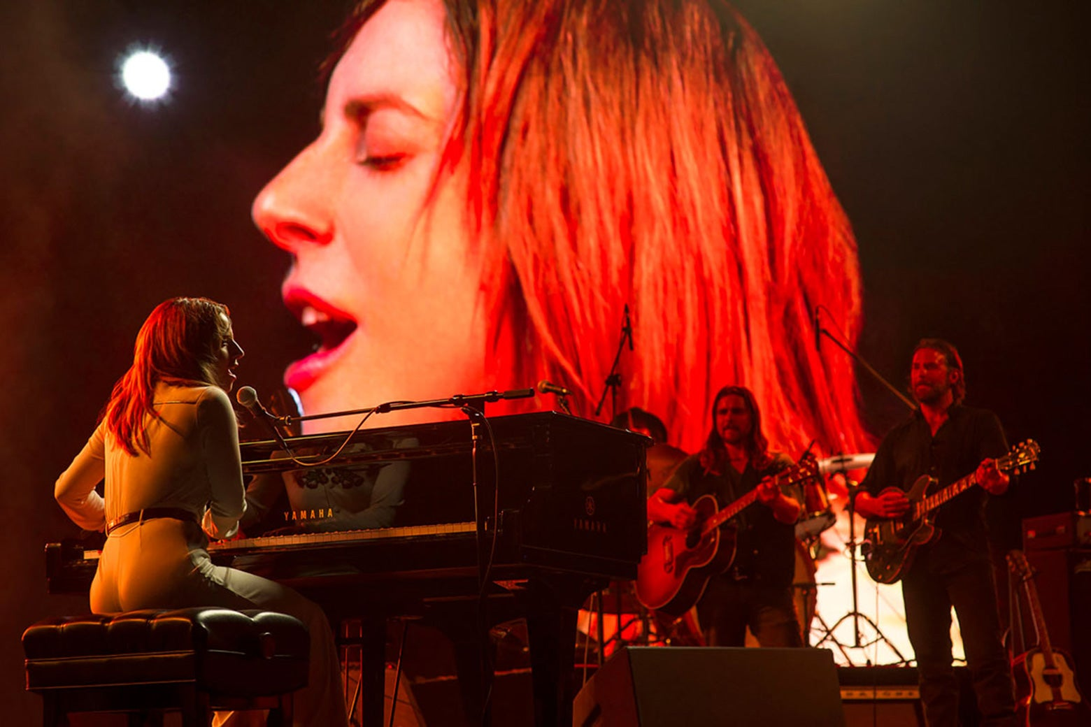Lady Gaga at the piano and Bradley Cooper on guitar, performing on stage in A Star Is Born.