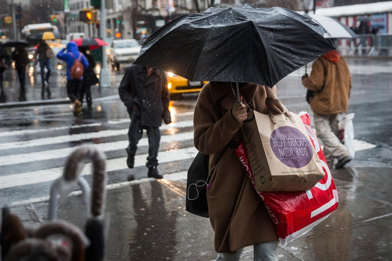 A woman crosses the street in the rain, a black umbrella covering her face. She is carrying several shopping bags.