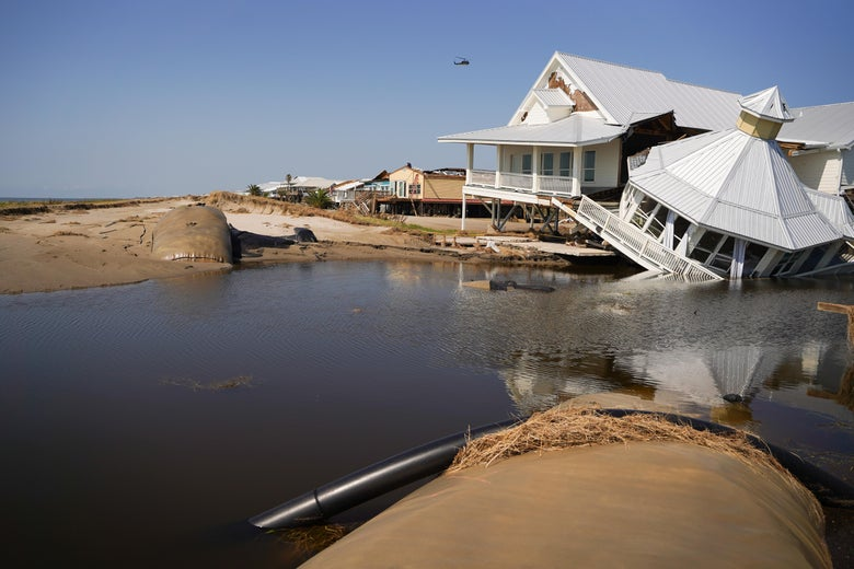A beachfront house on stilts on a clear day. Half of it has sunk into the rising water.