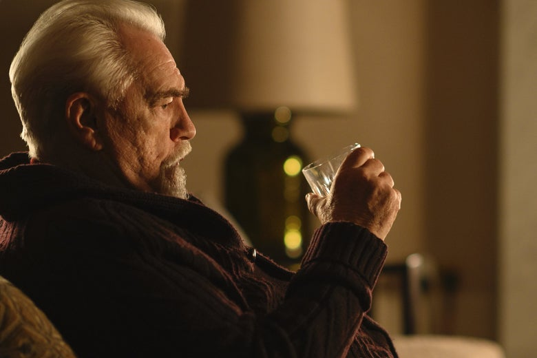 Brian Cox pouts on a couch holding a glass.