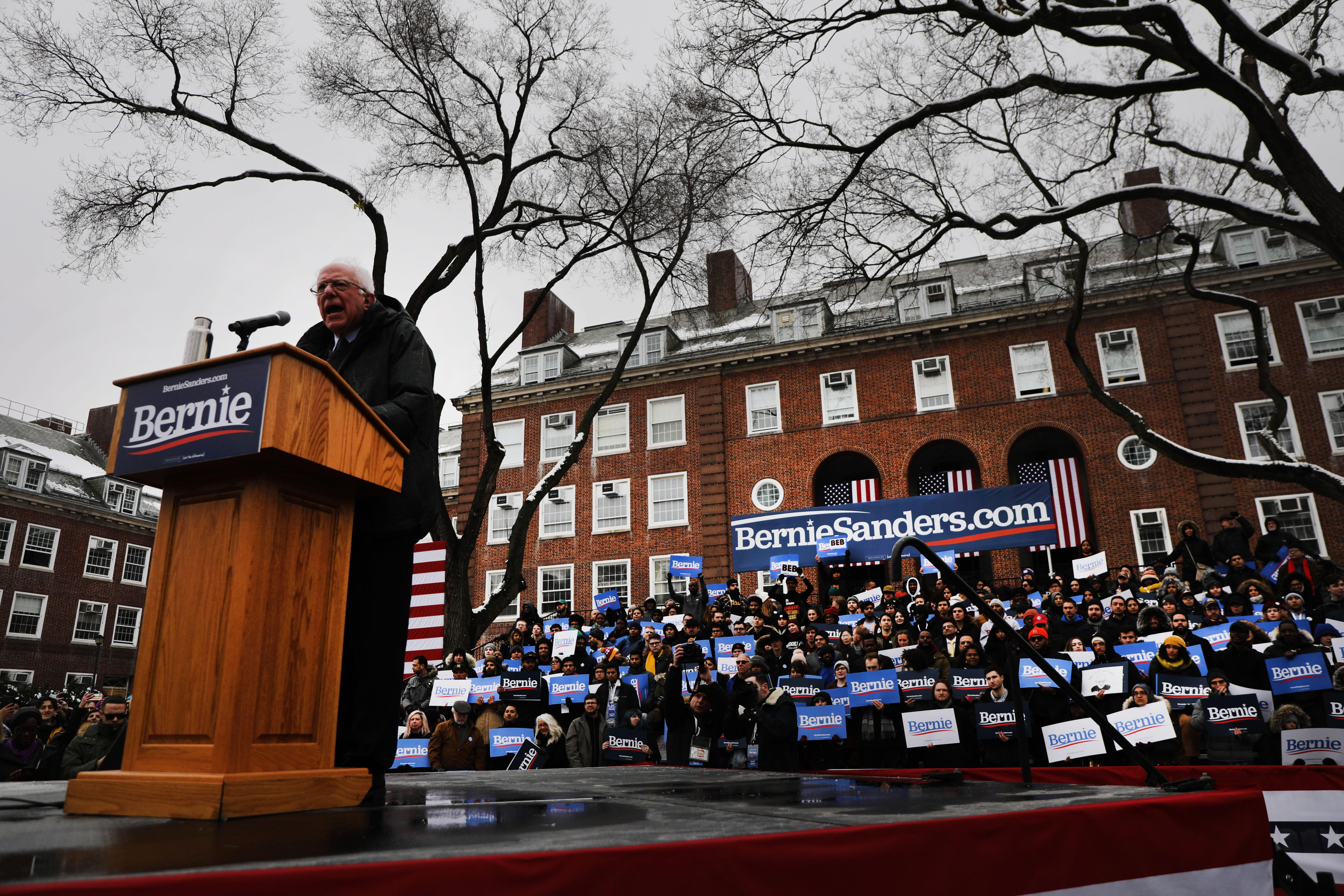 Bernie Sanders stands at a podium on a stage outdoors in front of supporters.