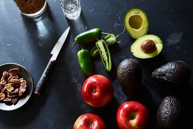 Three red apples, four avocados, and three jalapeño peppers lie on a black surface, along with a knife and a small bowl of pecans. One of the avocados and one of the peppers are each cut in half, lengthwise.