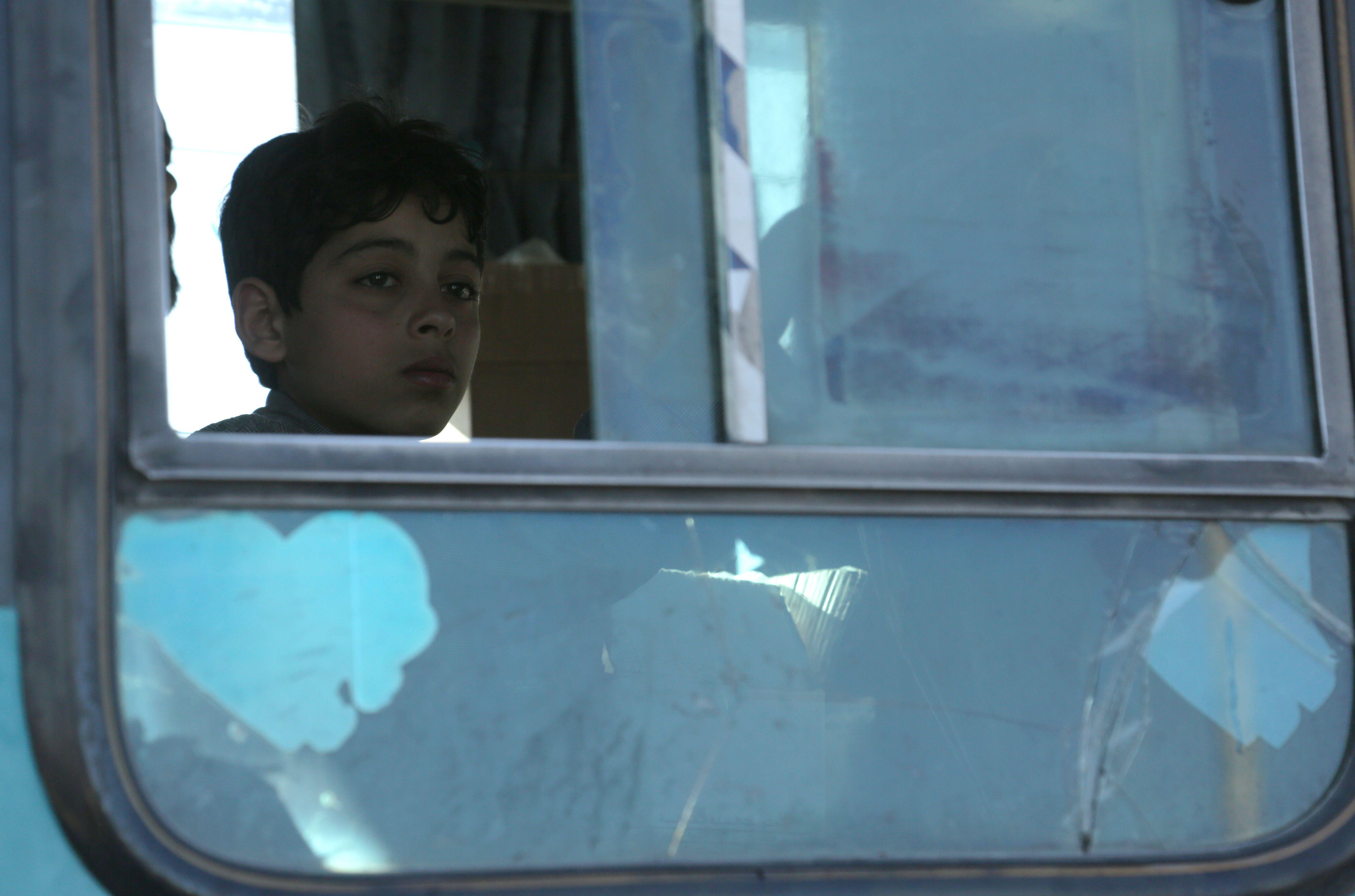 A Syrian child looks out a bus window.