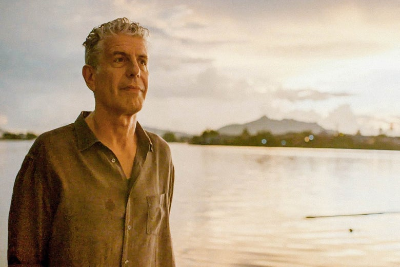 Anthony Bourdain stands in front of a body of water reflecting an orange sky.