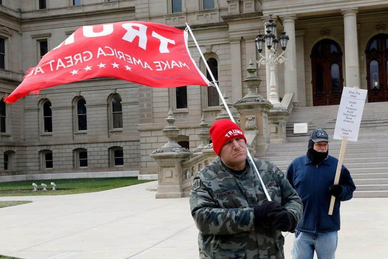 One man in a red Trump beanie carries a large red Trump flag and another man holds a Stop the Steal sign in front of the Capitol steps