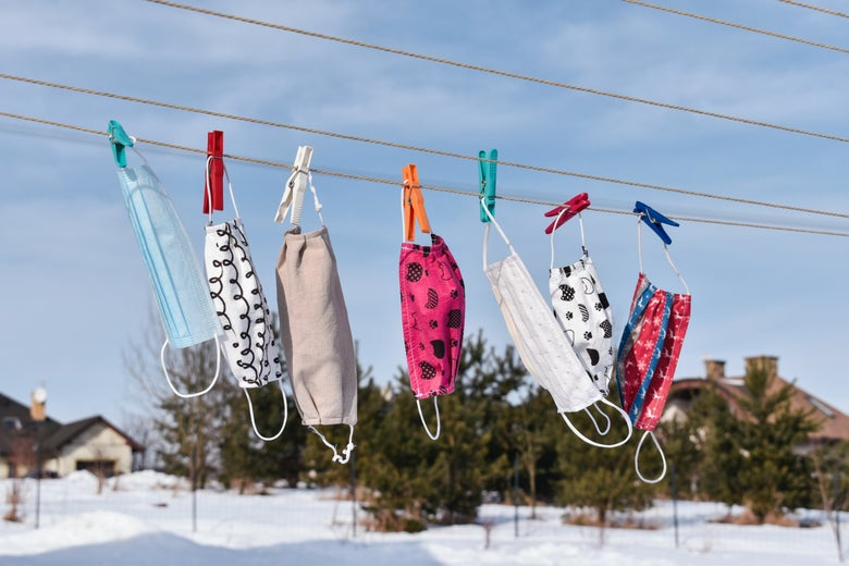 Masks in various colors and designs hanging on a clothesline outside in a snowy area