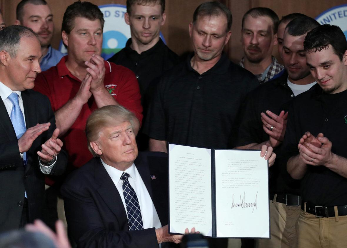 "U.S. President Donald Trump holds up an executive order on ""Energy Independence."""