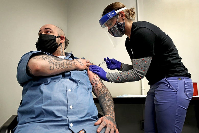 A woman gives a man with tattooed arms a shot.