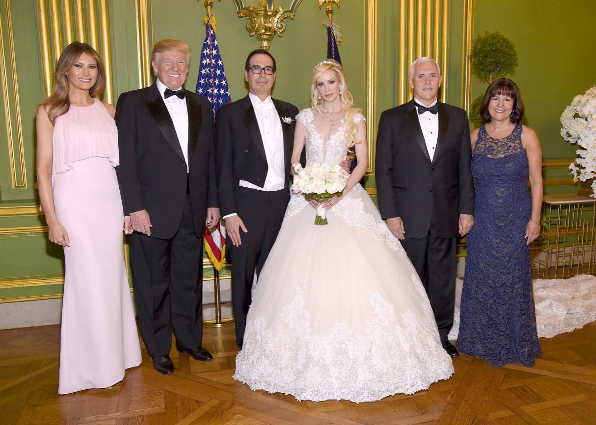 First Lady Melania Trump, President Donald Trump, Secretary of the Treasury Steven Mnuchin, Louise Linton, Vice President Mike Pence, and Second Lady Karen Pence pose at the wedding of Secretary of the Treasury Steven Mnuchin and Louise Linton on June 24, 2017 at Andrew Mellon Auditorium in Washington, DC. Louise Linton is wearing a custom Ines Di Santo gown with wedding ring and earrings by Martin Katz.