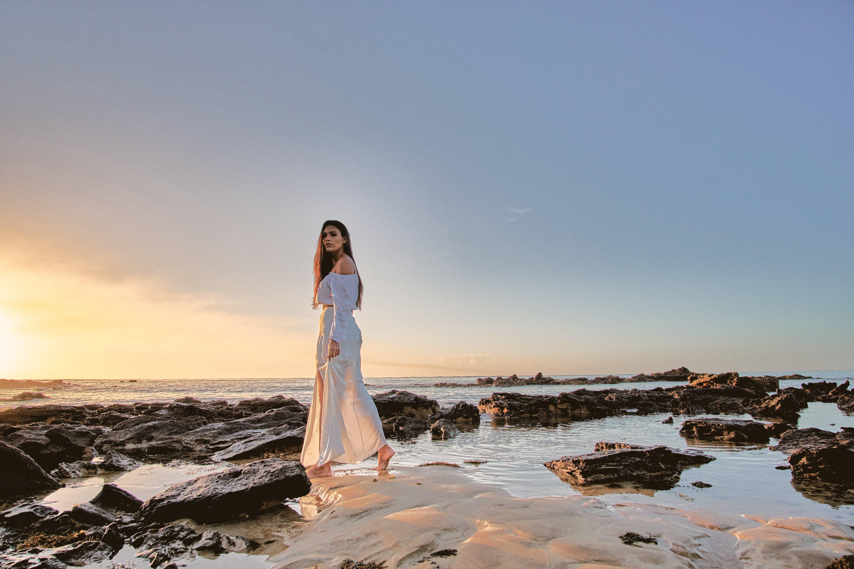 A woman in a white dress walks through a creek.