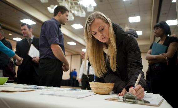 Jenny Pazar, who is currently an intern, fills out a form as she looks for a job at a job fair Dec. 02, 2011, in Portland, Ore.