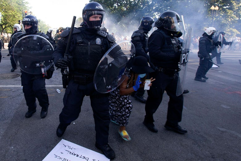 Police in riot gear surround a protester
