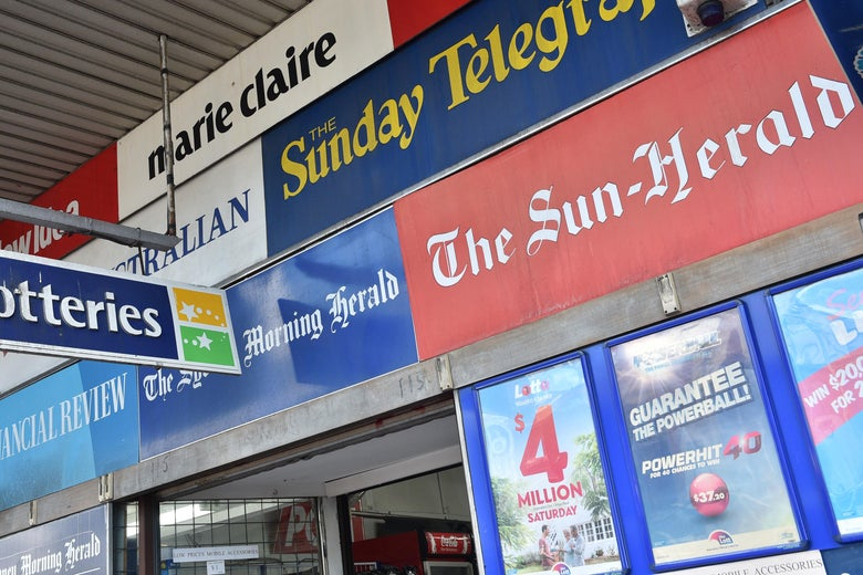 Advertisements for the Sydney Morning Herald, the Sun-Herald, the Sunday Telegraph, and other Australia publications are seen on a building.