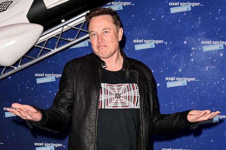 Elon Musk on a red carpet, shrugging.