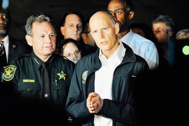 Florida Gov. Rick Scott speaks to the media as he visits Marjory Stoneman Douglas High School following a shooting that killed 17 people on Feb. 14 in Parkland, Florida.