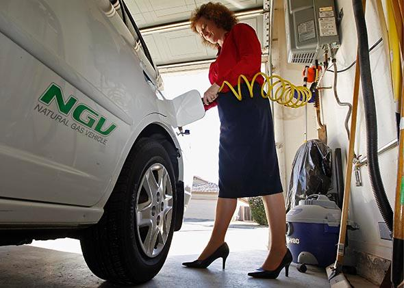 Connie Jones connects the nozzle of a home refueling station to her 2003 natural gas powered Honda Civic in the garage of her home in Chandler, Arizona, October 3, 2013.