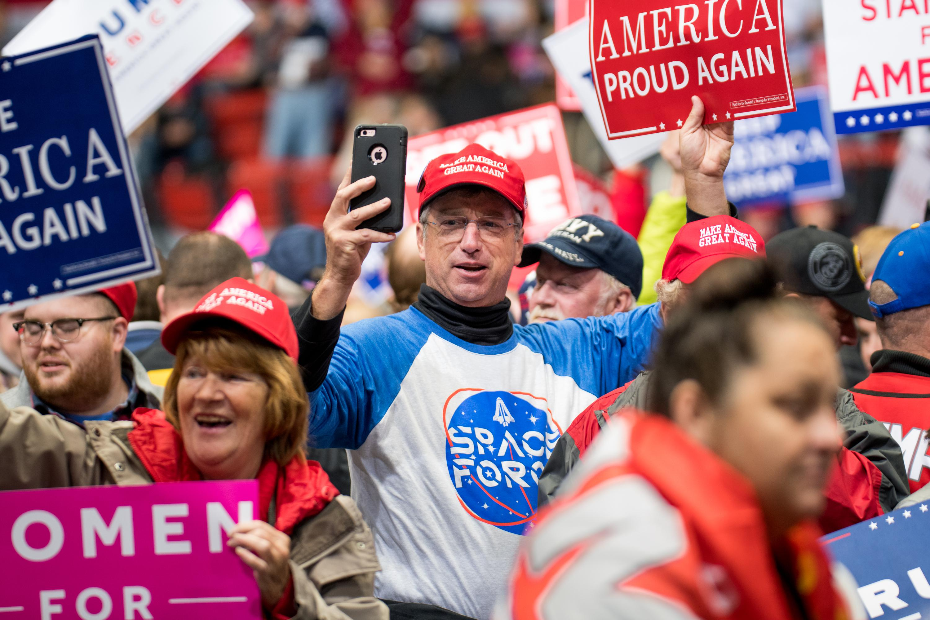 A man wearing a Space Force shirt and a MAGA hat holds his phone up to document the crowd at a Trump rally. The energetic crowd around him holds pro-Trump signs.