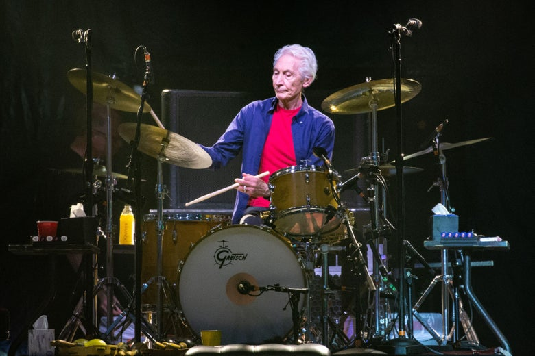 A man in a red t-shirt with a blue overshirt plays the drums on a stage.