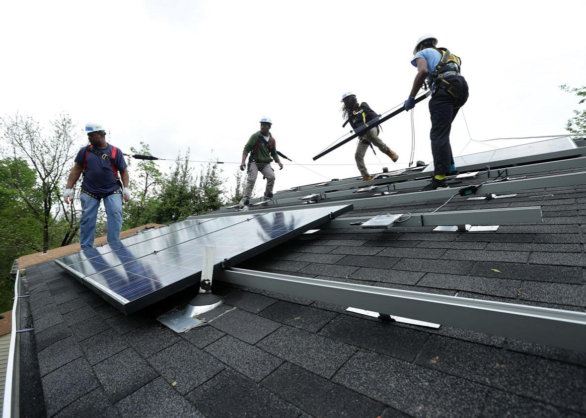 Workers put solar panels down during an installation May 3, 2016 in Washington, DC.