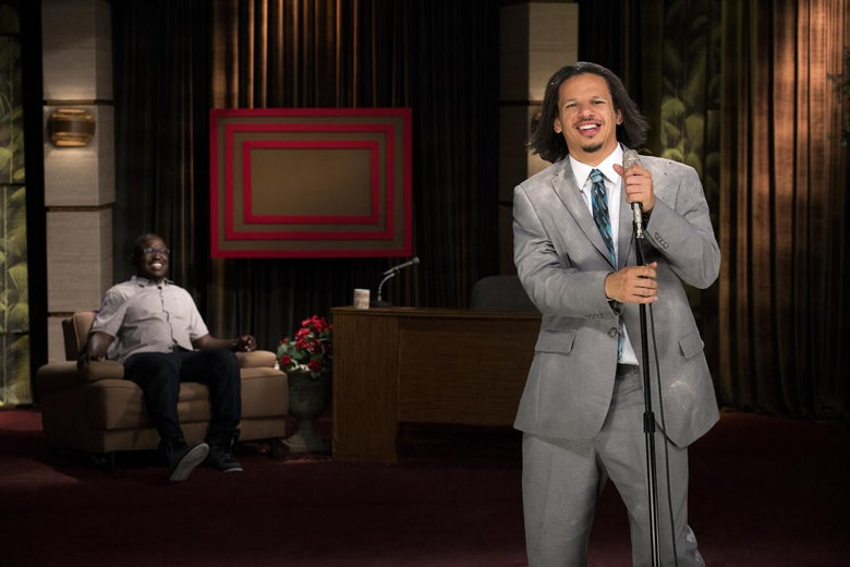 Eric Andre stands at a microphone with Hannibal Buress seated in an armchair in the background.