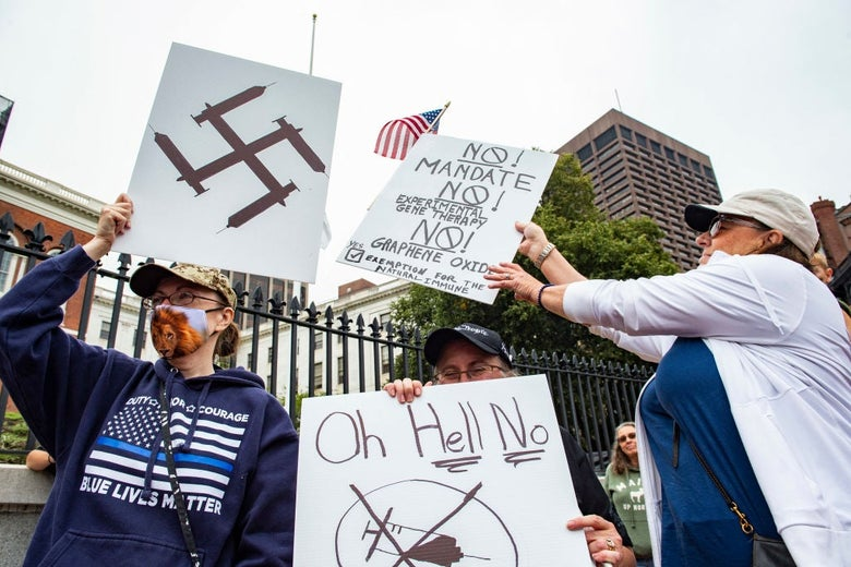 Three people outside the Massachusetts State House carry anti-vaccine signs, including one on which syringes form the shape of a swastika.