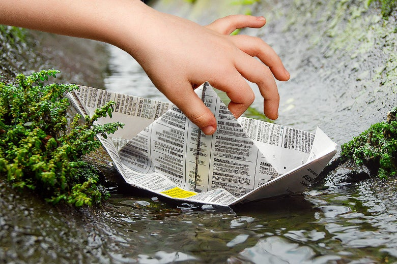A child's hand gently pulling a newspaper boat out of a gutter.