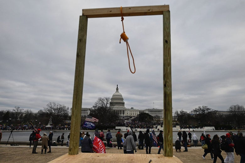 A noose hangs outside the Capitol building. Pro-Trump demonstrators congregate nearby.