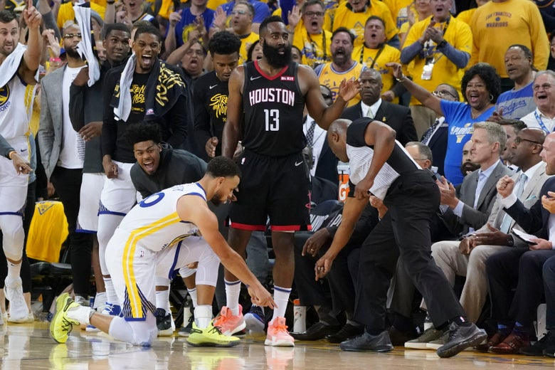 Curry, kneeling, points at the sideline as Harden looks past him with a stoic expression.