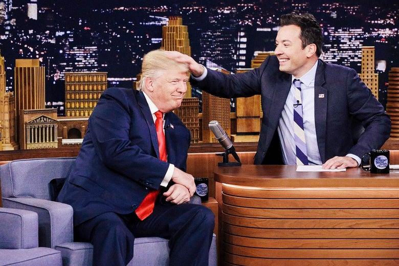A smiling Jimmy Fallon musses Trump's hair with his hand.