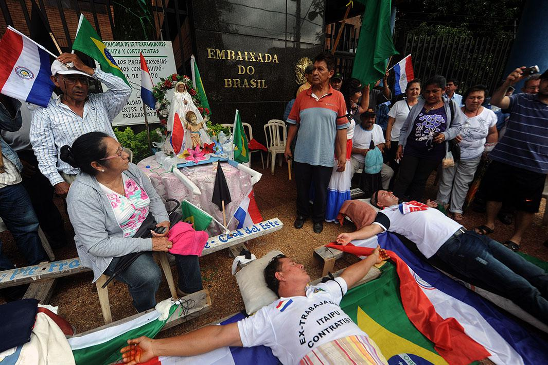 "Two former employees of Unicom, contractor of the Itaipu Dam, lie on crosses after being ""crucified"" by fellow co-workers during a protest in front of he Brazilian embassy in Asunción, Paraguay, on Nov. 12, 2014. They were demanding compensation benefits after the two workers were fired from their jobs. The Itaipu hydroelectric dam, the second-biggest in the world after China's Three Gorges facility, straddles the Brazil-Paraguay border"