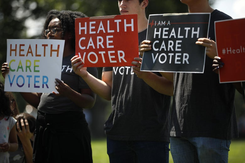 "Three protesters hold signs reading ""Health Care Voter"""