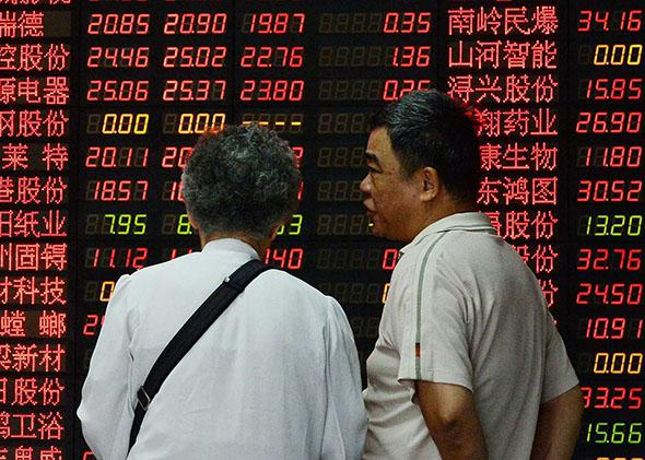 Investors talk in front of a board displaying share prices at a security firm in Shanghai on July 1, 2015. Shanghai shares closed down more than five percent on July 1, resuming their downward trajectory a day after recording their biggest gains in more than six years.