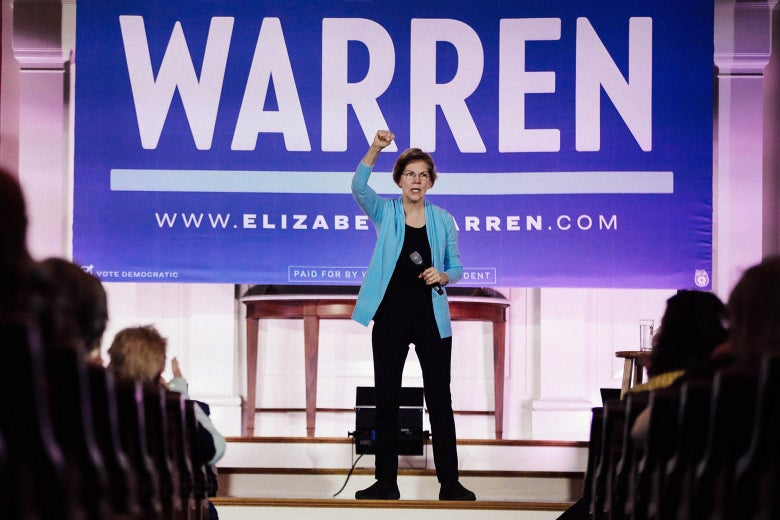 Elizabeth Warren raises her fist and holds a mic in front of a banner bearing her name at a campaign event.