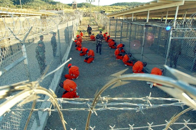 Men in orange jumpsuits kneel in an enclosed area.