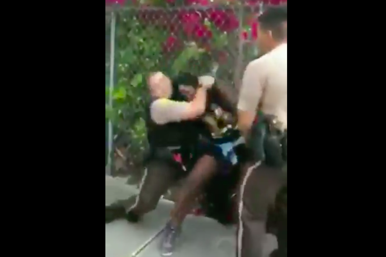 A screengrab from the video showing the officer pulling the woman down in a headlock