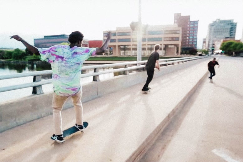 Three skateboarders skate across a bridge, away from the camera, from Minding the Gap.