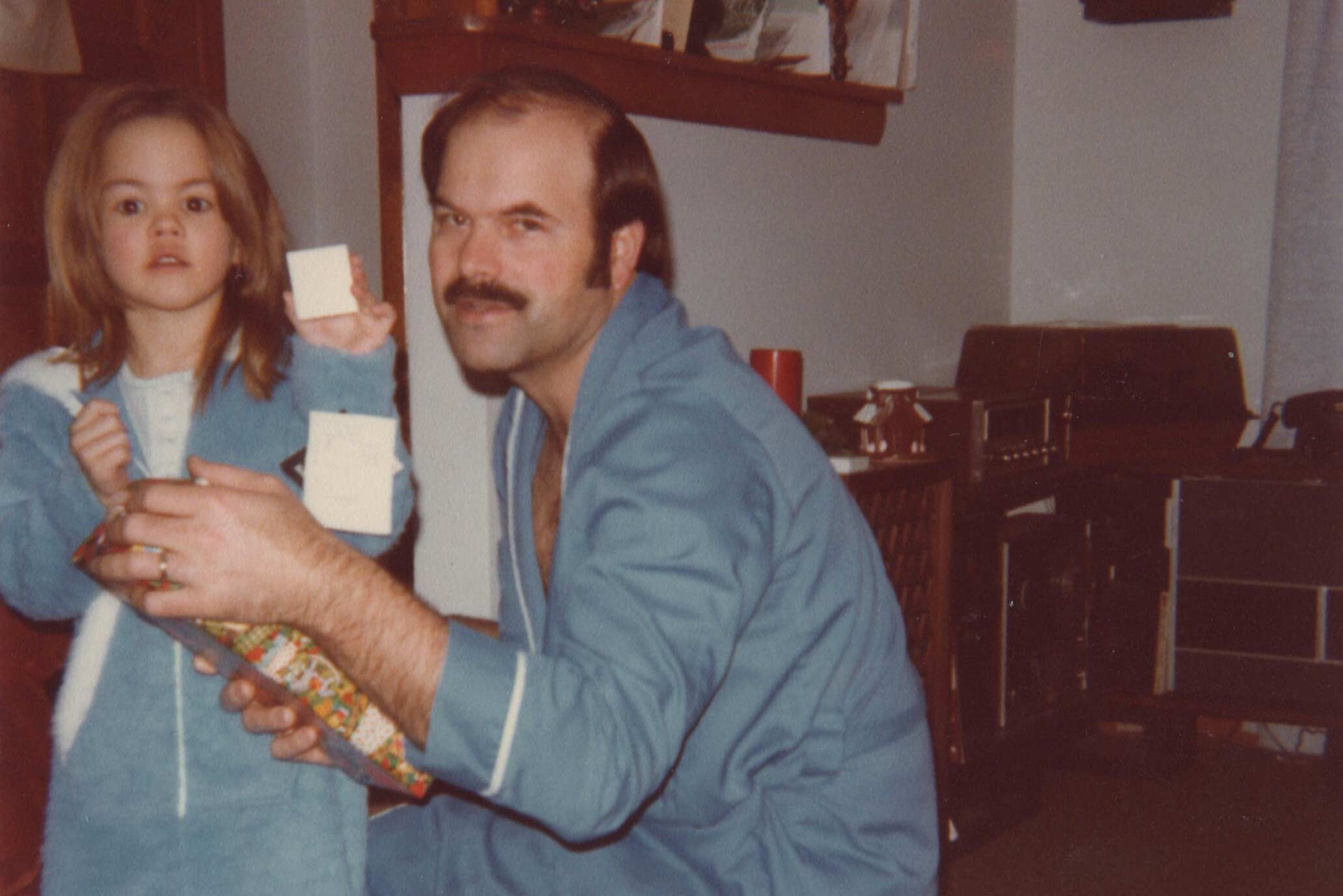 A young girl and her father open a present while wearing pajamas.