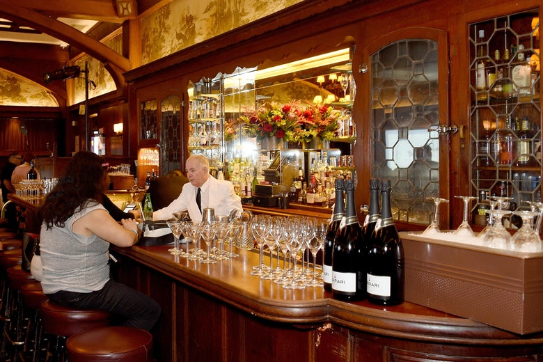 A bartender in a white jacket and black tie serves a customer at the bar in the new room at the Musso & Frank Grill in Hollywood.