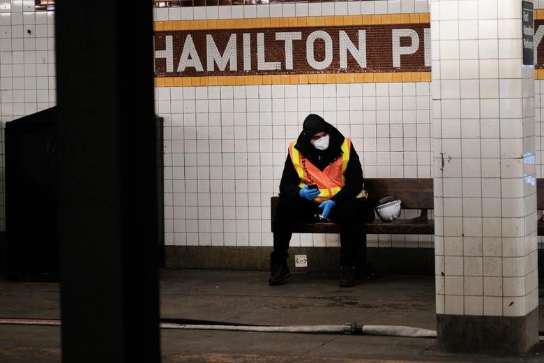 A worker wearing an orange vest and a face mask sits on a bench at a subway station.