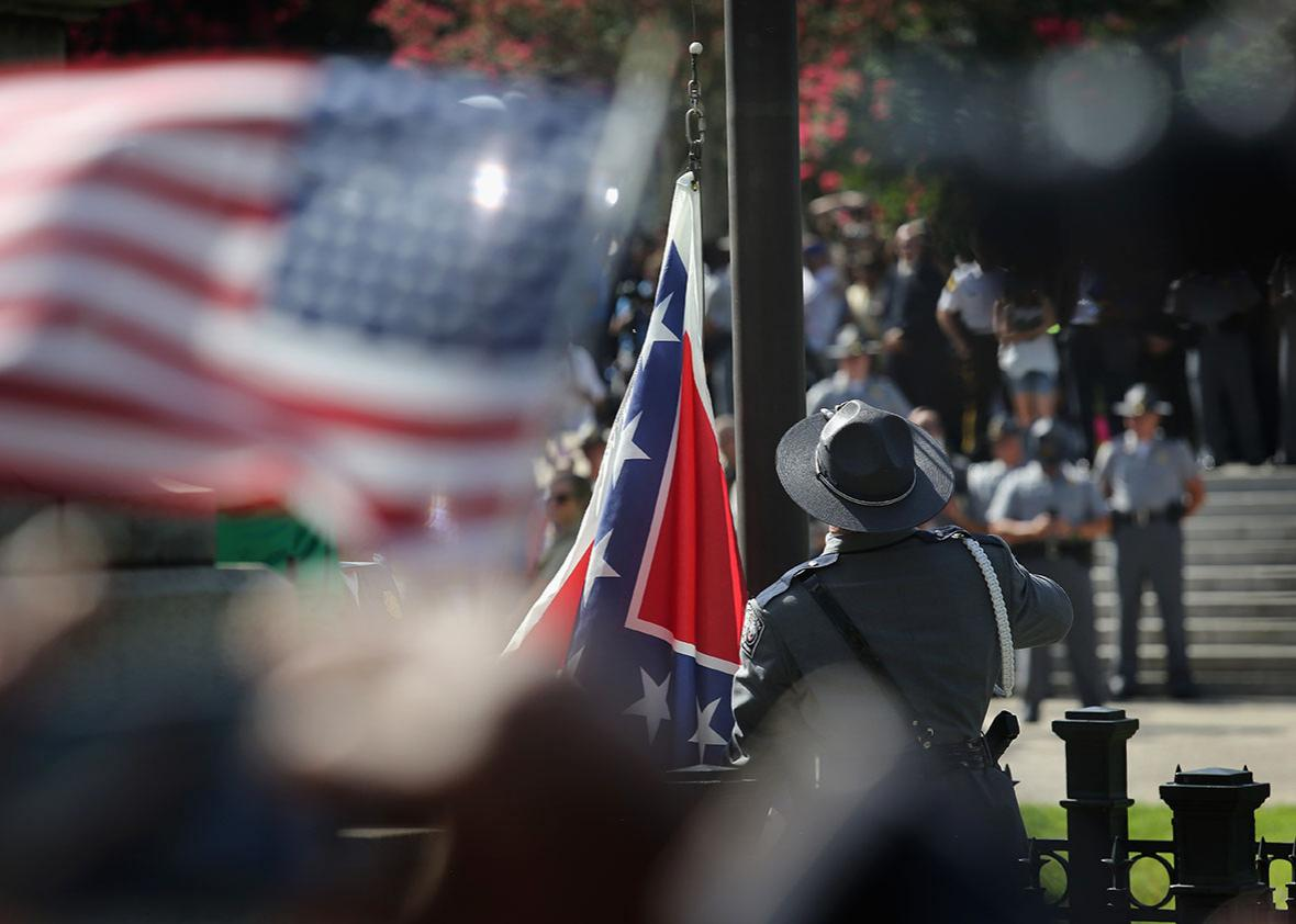 A South Carolina state police honor guard lowers the Confederate