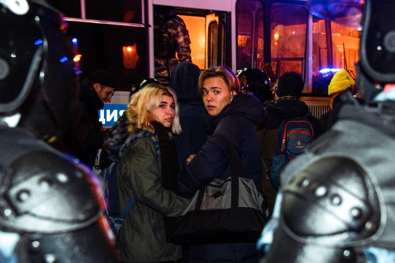 Two women flanked by armored police officers look back toward the camera as they are forced onto a police bus.
