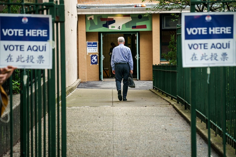 "A voter enters a Brooklyn polling station on Thursday to vote in New York state's primary election. The signs saying ""vote here"" are listed in English, Spanish, and Japanese."