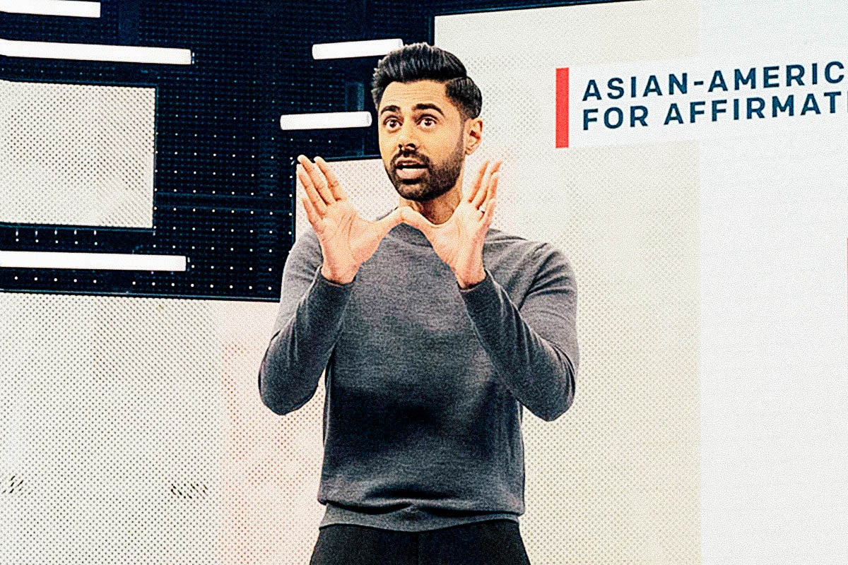 Hasan Minhaj on stage with a chart.
