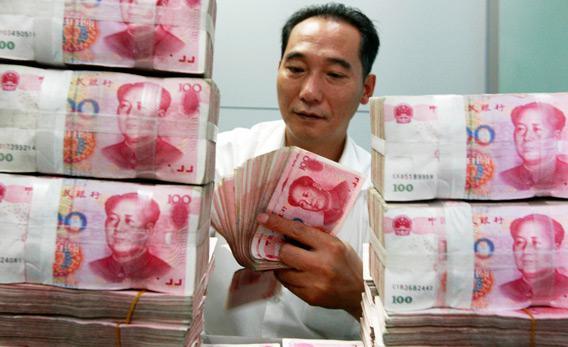 A Chinese bank worker counts stacks of 100-yuan notes at a bank.