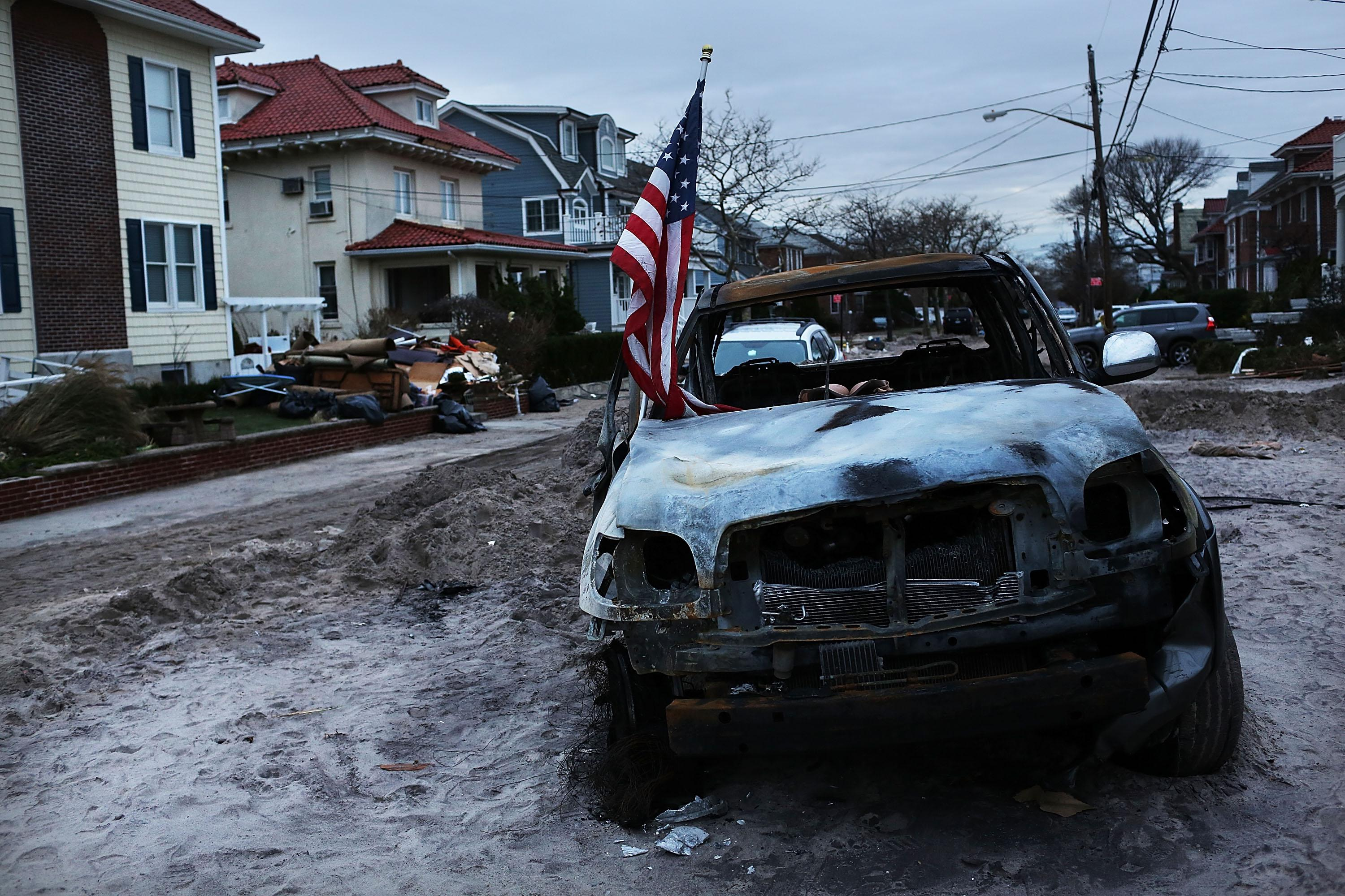 A destroyed car sits in the street in the heavily damaged Rockaway neighborhood, in Queens where a large section of the iconic boardwalk was washed away on November 2, 2012 in New York.